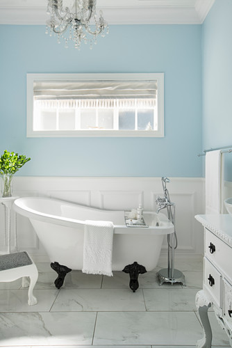 Free-standing bathtub in bright bathroom with pale blue walls and marble tiles