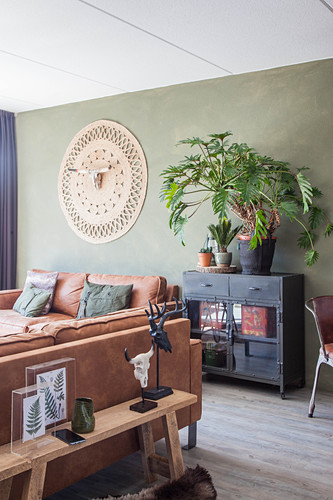 Leather sofas, houseplants on black cabinet and wall hanging with animal skull in living room