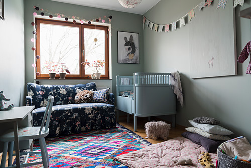 Pale blue cot, sofa and play mat in nursery