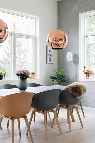 Table and shell chairs below copper pendant lamp in bright dining room