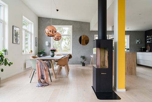 Table and shell chairs behind log burner in open-plan interior