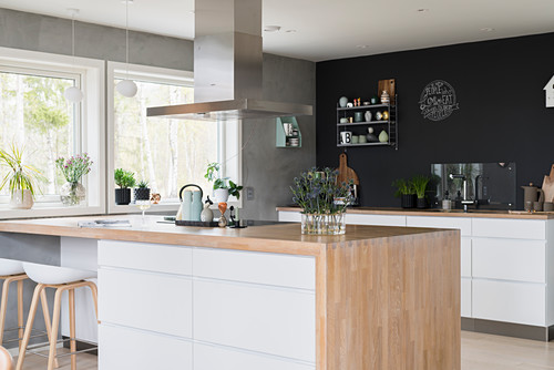 Island counter with pale wooden worksurface and kitchen counter against black wall in open-plan kitchen