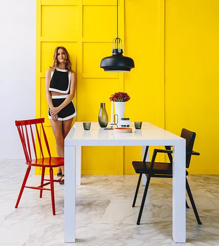 Weißer Tisch mit Stühlen im Essbereich, junge Frau vor gelber Kassettenwand