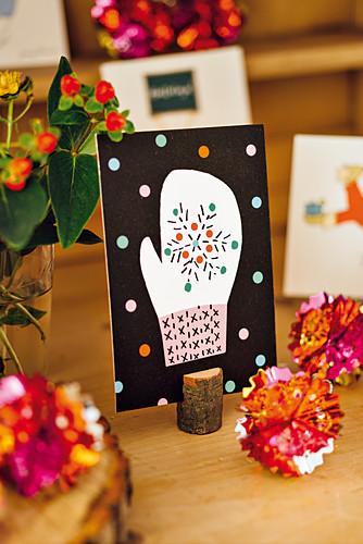 Postkarten mit Wintermotiv in Tischkartenhalter aus Holz und Kugeln aus glänzendem Stanniol