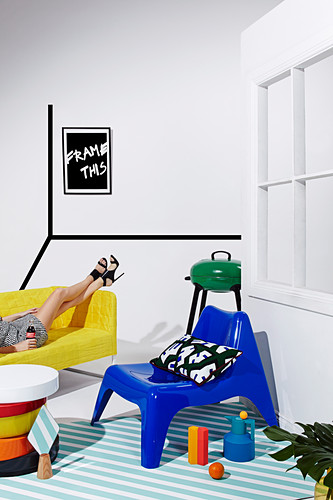 Blauer Plastikstuhl auf diagonal gestreiftem Teppich im Studio