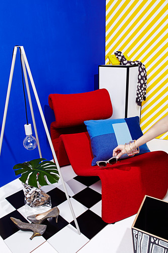Hand puts sunglasses on red designer armchair against blue wall