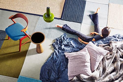 Verschiedene Teppichmuster, Frau sitzt auf dem Boden vor Bett mit Kuscheldecke