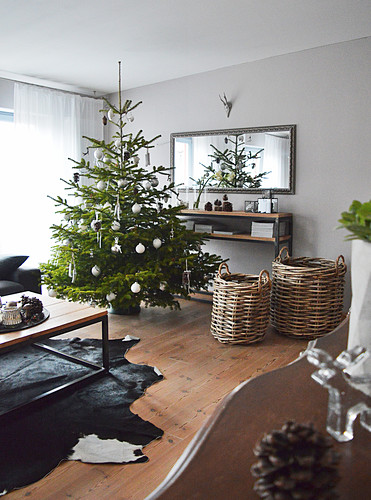 Decorated Christmas tree, baskets next to sideboard and wall-mounted mirror in living room
