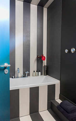 Striped pattern in bathroom running over ceiling, wall, bathtub and floor