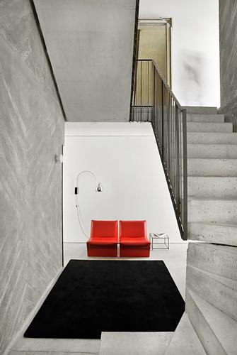 Rote Sessel, Bogenlampe und Beistelltisch im Foyer, im Vordergrund Betontreppe