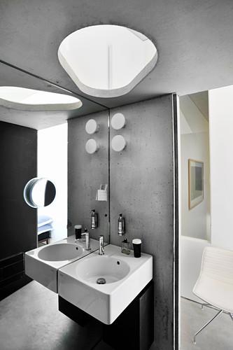 Twin sinks on concrete wall in bathroom