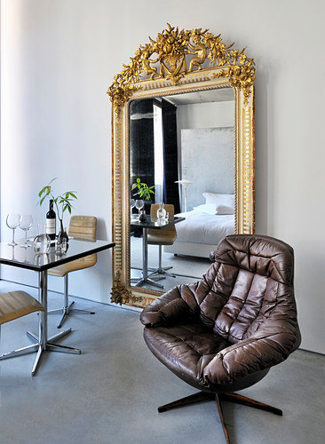 Bistro table and chairs next to large mirror with ornate gilt frame an leather swivel armchair