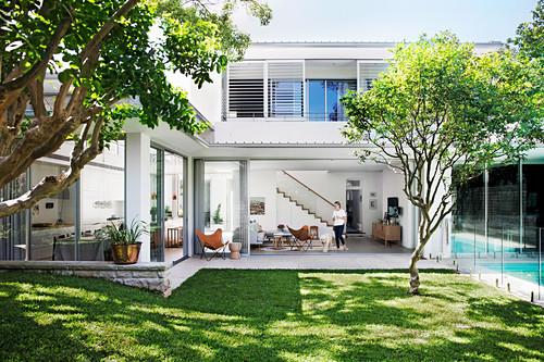 Blick vom Garten in ein luxuriöses Haus mit Glasfronten
