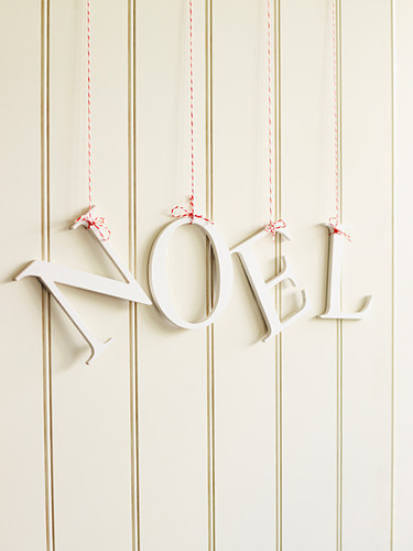 The letters 'Noel' hung on a white wooden wall