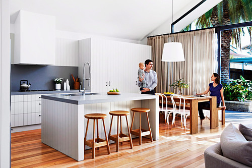 Open kitchen with kitchen island and dining area in front of patio door, family with small child at the dining table
