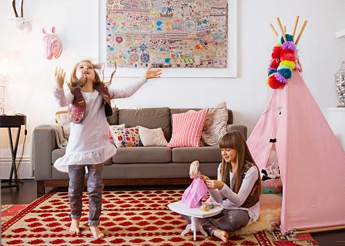 Spielende Mädchen auf gemustertem Teppich vor rosa Tipi im Wohnzimmer