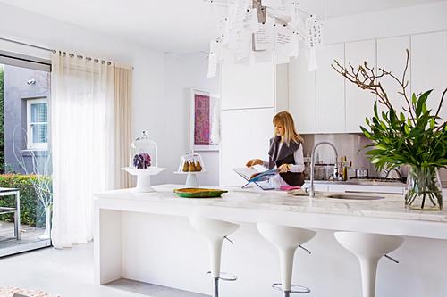 weiße Einbauküche mit Kücheninsel und Barhockern, Frau im Hintergrund