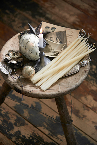 Candles, vintage ornaments and old photos on wooden stool
