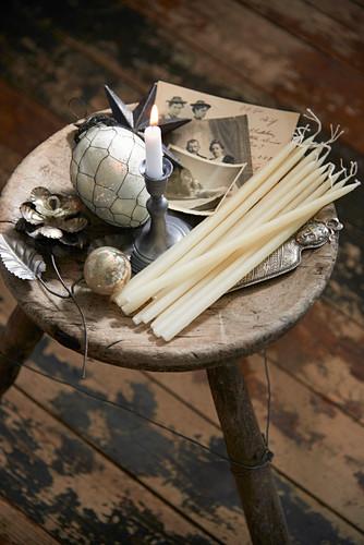 Kerzen, nostalgische Deko und alte Fotos auf einem Holzschemel