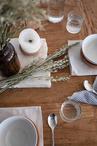 Place setting, candle and ears of cereal on rustic wooden table