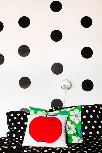 Black, DIY, polka-dot stickers on white wall above sofa