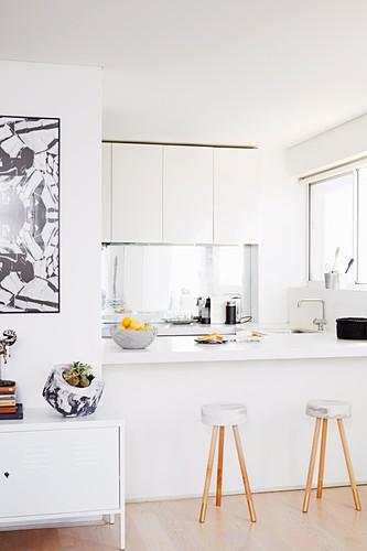 Selbstgemachte Barhocker vor der offenen Küche in Weiß