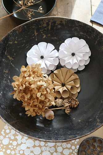 Dried hydrangea and origami flowers in dish