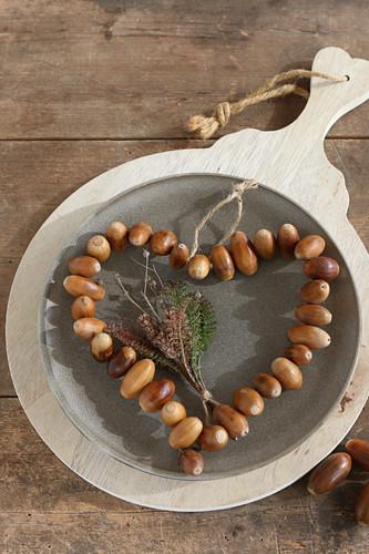 Heart of threaded acorns on plate on board