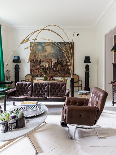 Brown leather sofa set and Italian designer lamp in living room with huge painting in background