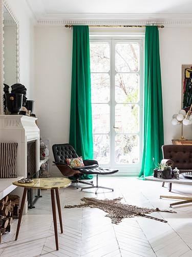 Lounge Sessel vor Fenster, im Vordergrund Kamin und Beistelltisch im Wohnzimmer