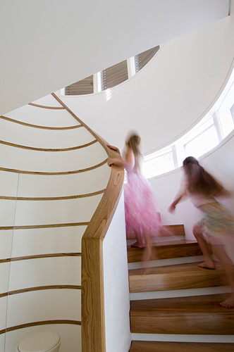 Two girls running up spiral staircase with wooden treads in white stairwell