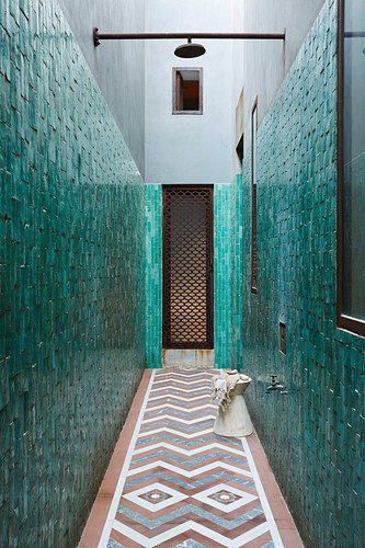 Outdoor shower in the narrow courtyard with tiled walls
