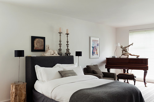 Piano in spacious bedroom with double bed, candelabras and sphinx statue