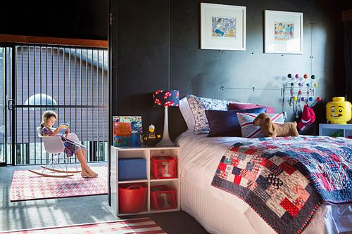 Kind im Schaukelstuhl im Kinderzimmer mit schwarzer Wand