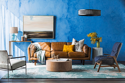 Brown leather couch, armchair and coffee table in the living room with blue wall