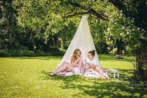 Two friends sitting under DIY canopy in garden