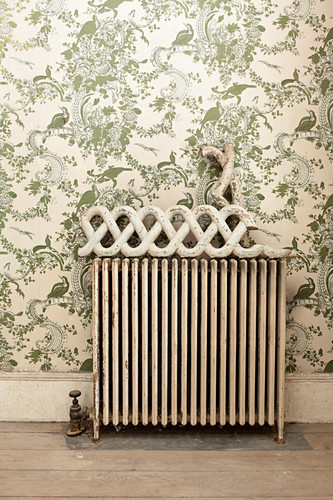 Ornament on top of old radiator against green-patterned wallpaper