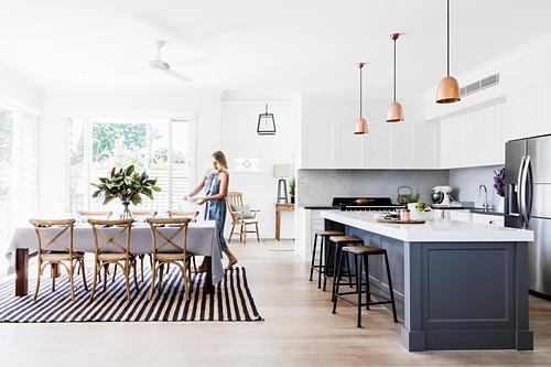 Offene Küche mit Kücheninsel, im Hintergrund Frau am gedeckten Tisch