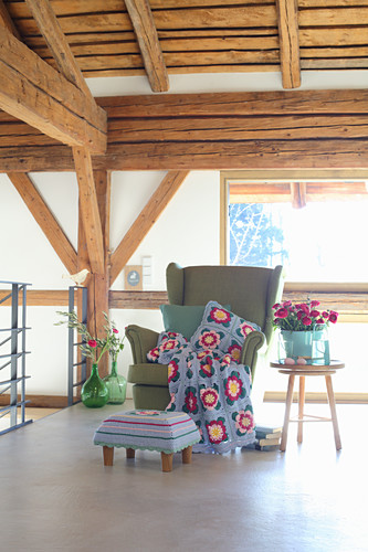 Crocheted blanket and cushion on wingback armchair in country house
