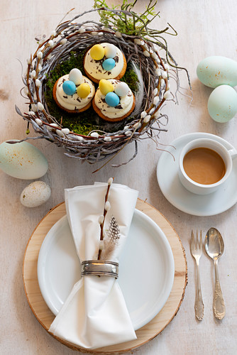 Cupcakes in handmade pussy willow Easter nest, place setting and cup of coffee