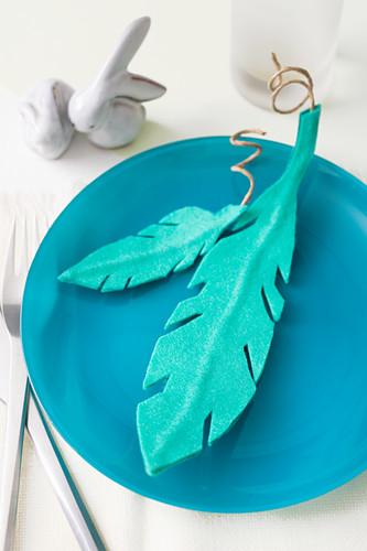 Federn aus türkisfarbenem Filz auf blauem Teller