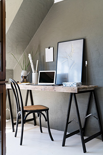 Desk made from trestles against grey wall below sloping ceiling