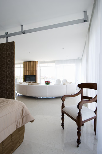 Armchair and bed in sleeping area with white designer sofa next to glass wall in background