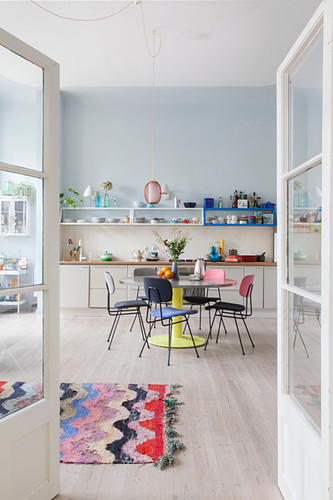 Colourful retro furniture in open-plan kitchen-dining room seen through double doors