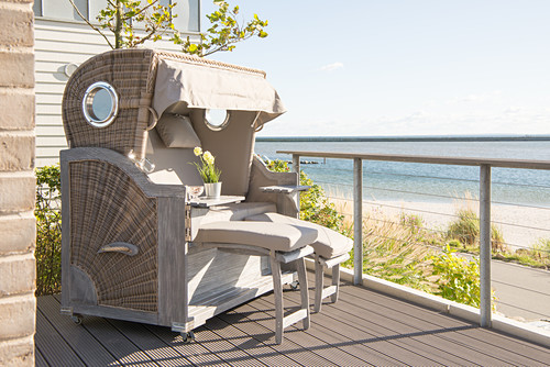 Wicker beach chair on wooden terrace with sea view
