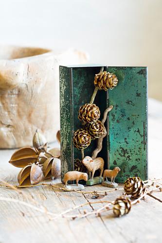Geschnitzte Krippenschafe und Lärchenzapfen in einer alten Blechdose