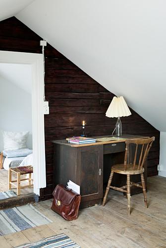 Alter Schreibtisch vor einer rustikalen Holzwand unter dem Dach