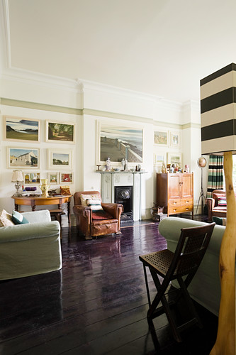 Distressed french leather armchairs in living room with artwork and surfaces adorned with figures
