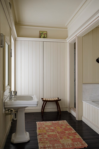 Wood panelled bathroom with African rug and stool
