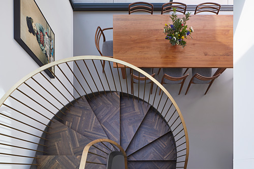 View down spiral staircase to dining table